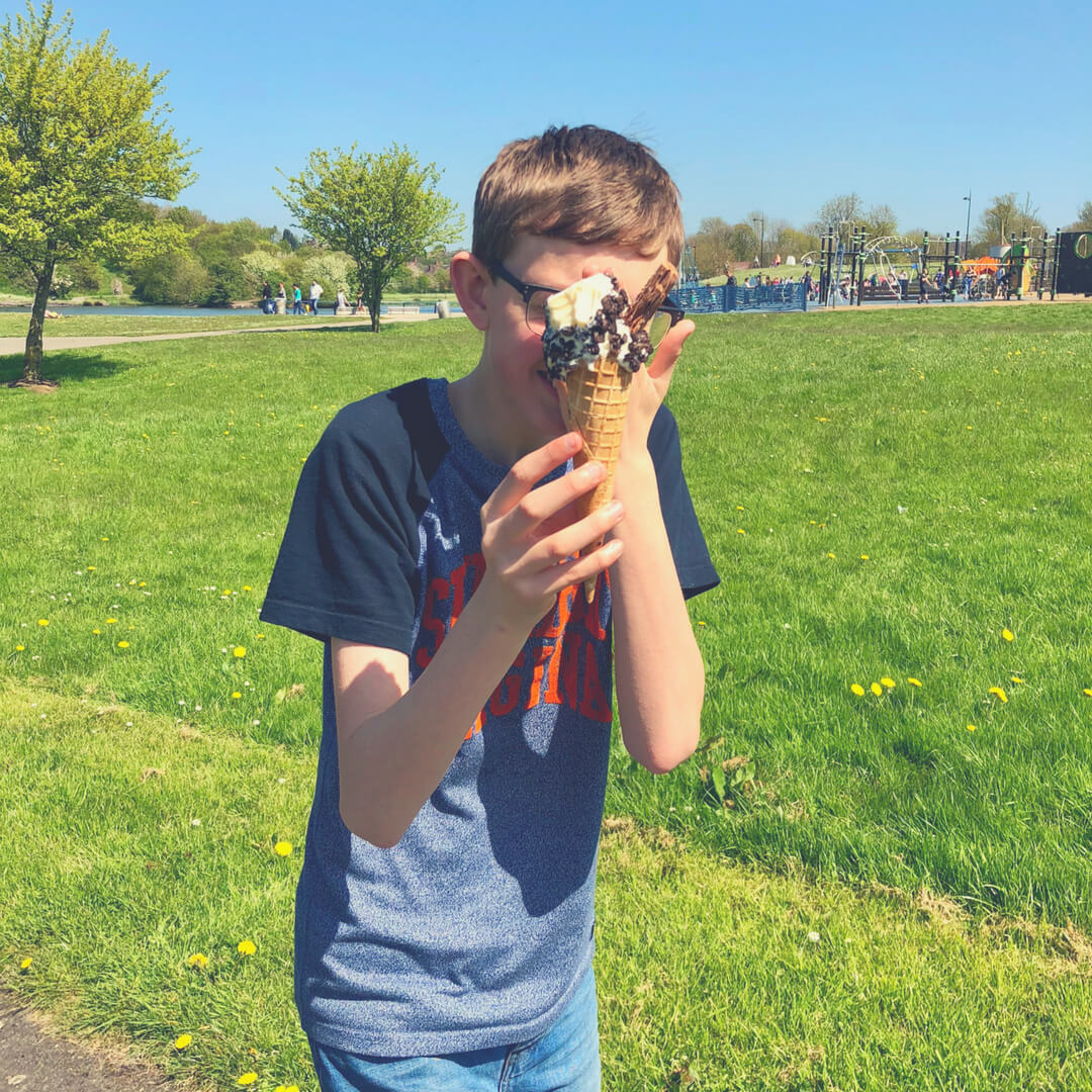 Teen boy holds an ice-cream in front of his face.