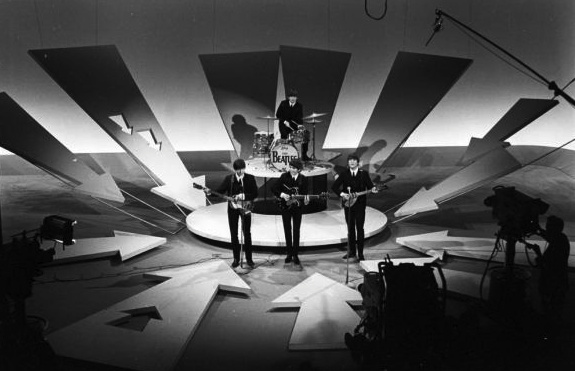 High crane shot of The Beatles on set of 'The Ed Sullivan Show' with full stage and cameras in view