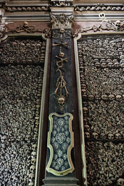 Columnas de color negro decorados con cintas, calaveras y cuadros de exvotos.