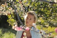 Louise observando una rama de un peral florecido