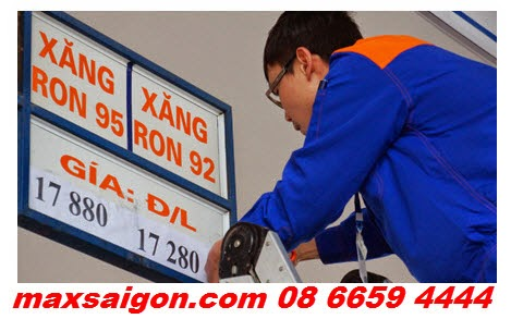 Nhân viên cây xăng đang điều chỉnh lại bảng giá xăng dầu