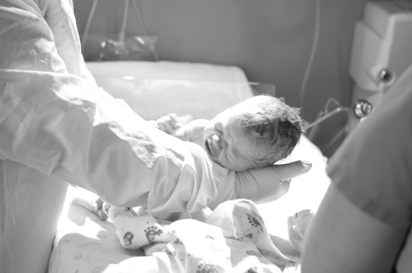 Doctor holds newborn baby after a delivery.