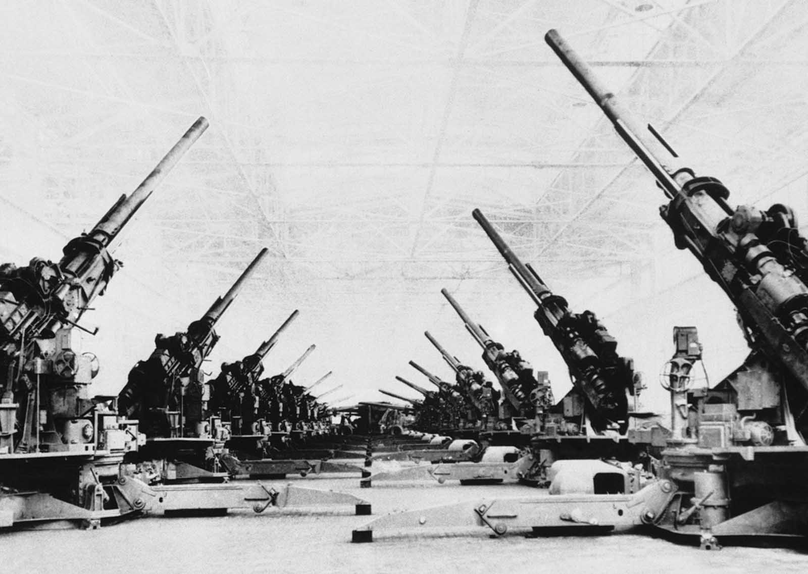 Huge anti-aircraft guns, the U.S. Army's new powerful Stratosphere guns, are lined up in the final assembly area of the Grand Rapids stamping division of Fisher Body in Detroit on June 1, 1944, prior to shipping.
