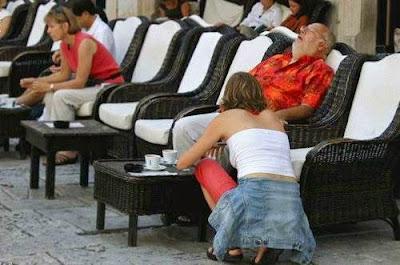 Mulher abaixada e homem descansando sentado em uma cadeira