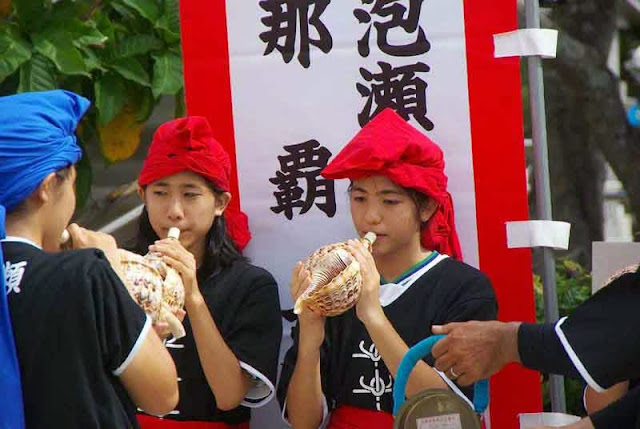 young girls blow conch shells as horns