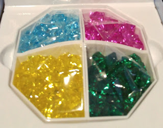 The plastic gems in their storage container in the game box. The containers are each diamond-shaped pentagons situated together so that they each form a quarter of an octagon in the box. The gems colours are yellow, green, blue, and pink.