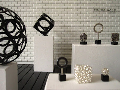 Modern miniature gallery space with a selection of round and square piece on display, and the words 'ROUND HOLE squared' on the back wall.