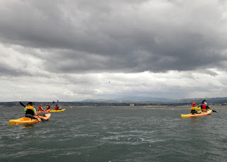 Kayaks on Monterey Bay under looming gray clouds, Monterey, California