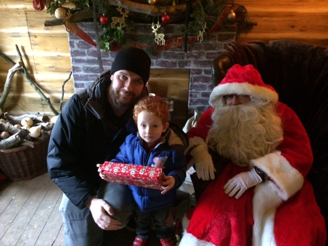 Daddy and son with a gift next to Santa