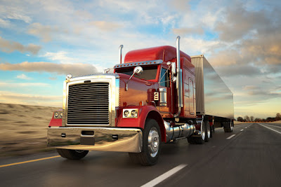 A photo of a semi-truck cruising down the highway.