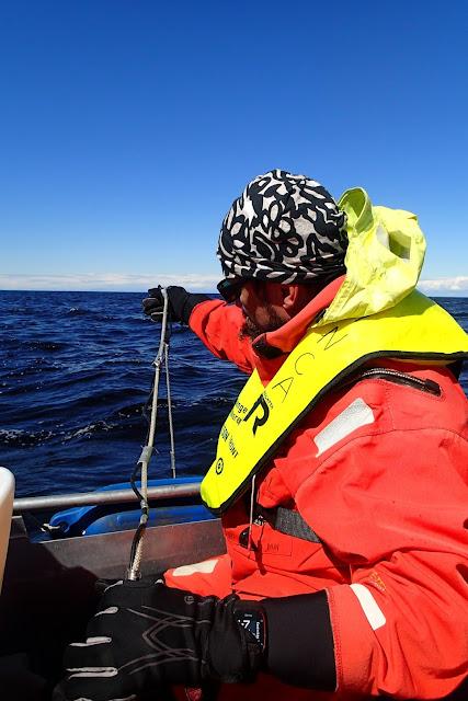 Pelastuspukuinen henkilö ottaa drop videota veneestä, eli laskee kameran köyden varassa mereen.