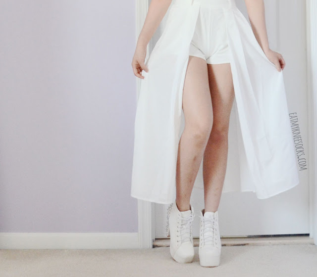 An all-white outfit featuring the Midnight in Paris flowy white maxi skort from Morrisday the Label, paired with a cropped white button-down shirt and white spiked platform booties.