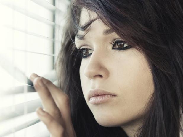Mujer en la ventana con miedo a quedarse soltera
