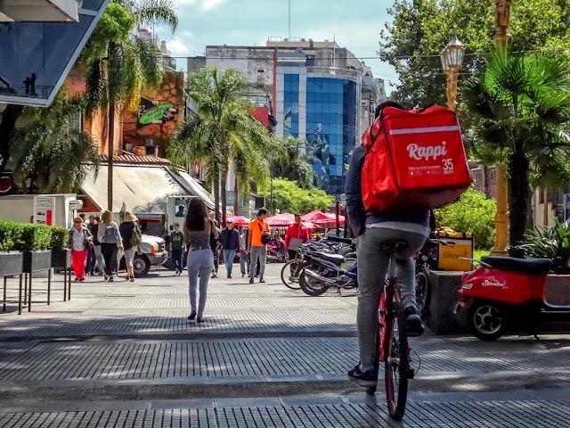 Un delivery en bici y gente caminando por Recoleta
