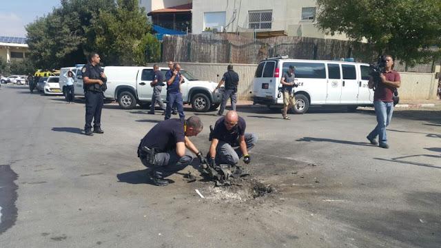 zapadores policía excavan pedazo de un cohete lanzado desde la Franja de Gaza que afectó a una carretera en la ciudad sureña de Sderot el 5 de octubre de 2016
