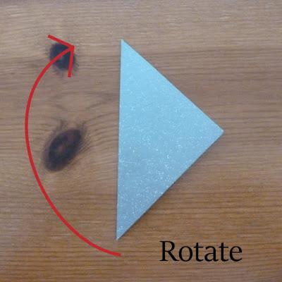 Red arrow showing rotation of paper tea bag folding christmas star