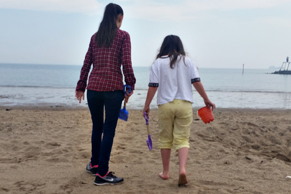 My two girls walking towards the sea on the beach