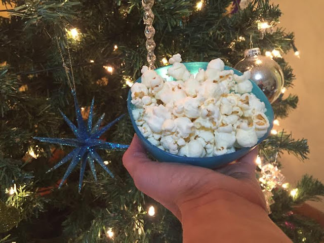 Enjoying white cheddar Wise Popcorn by the Christmas tree