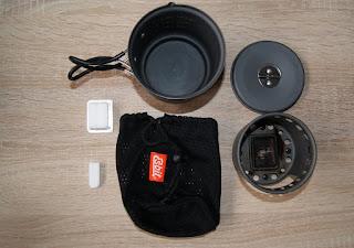 Hier sieht man die Einzelteile des Kochers. Oben rechts ein grauer Topf mit einem schwarzen, gummierten Griff. Daneben liegt der Deckel mit einem kleinen klappbaren Griff. Unter dem Deckel liegt der eigentliche Kocher mit diversen Luftöffnungen sowie einer schwarzen, bereits mit Brandspuren versehenen Innenpfanne. Neben dem Kocher liegt ein schwarzer Stoffsack, an den das Markenlogo von Esbit angenäht ist. Neben dem Sack liegen zwei weiße Brennstofftabletten
