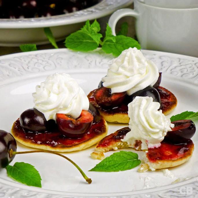 Luchtige pannenkoekjes met verse kersen, kersenjam en slagroom