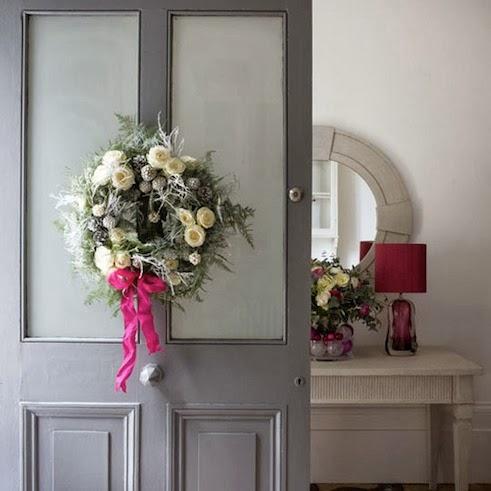 en la parte interna de la puerta de entrada se puede colocar una guirnalda o corona navidea que este decorada con pias y ramos