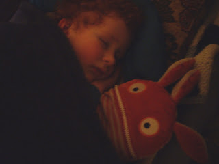 Child sleeping peacefully with Sorgenfresser Worry-Eater soft doll