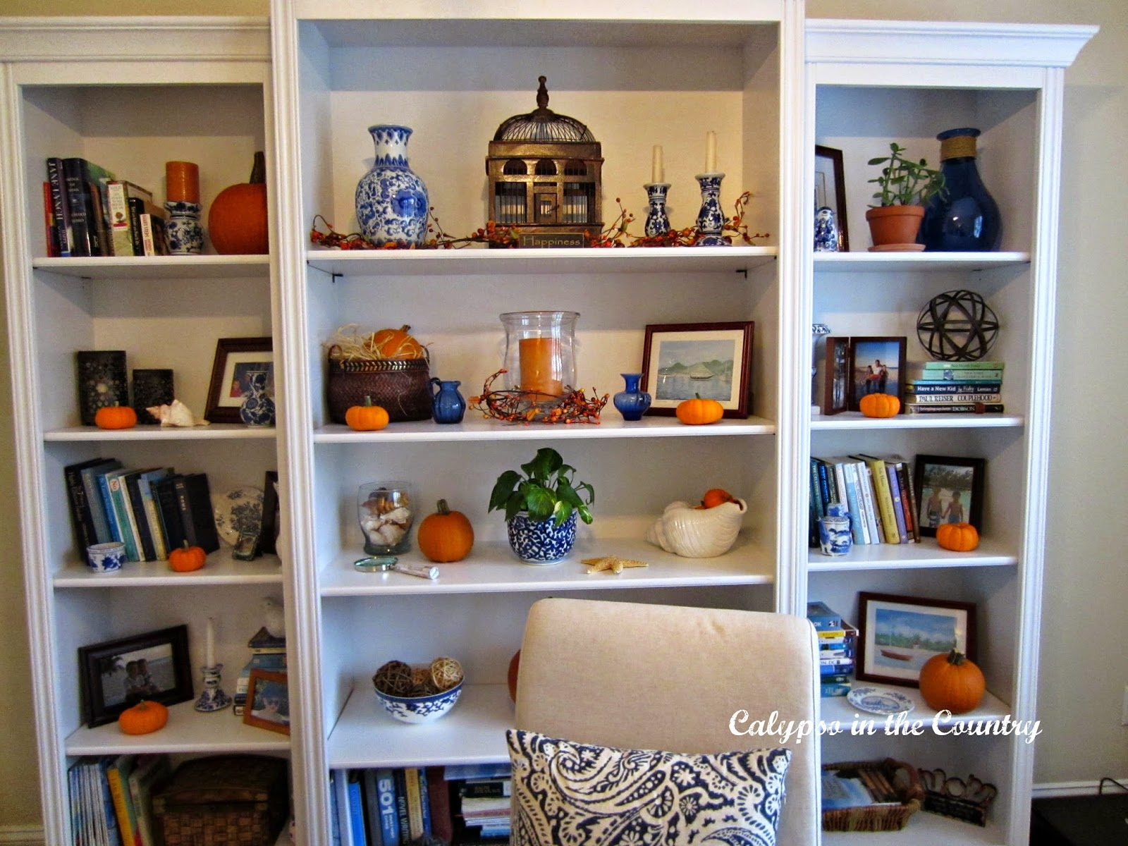 White bookcases decorated for fall