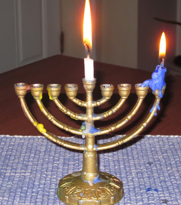 photo of a small traditional Chanukah menorah with the shamash and first candle lit