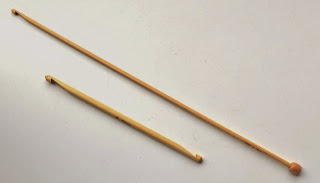 Two bamboo tricot hooks resting at a 45 degree angle. The longest is standard knitting needle length and 4 mm wide with a hook on one end and stopper on the other. The shorter one has a hook on each end.