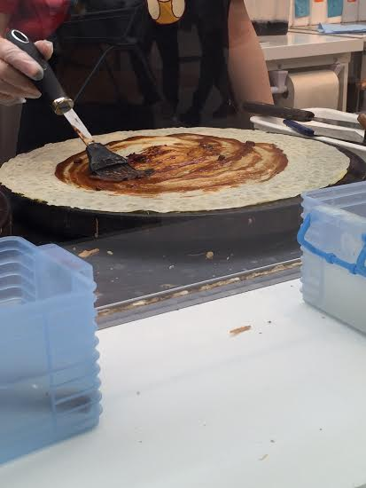 spicy sauce being applied to crepe;  crepe village