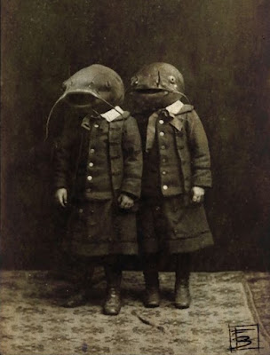 Old photo of two boys wearing fish heads
