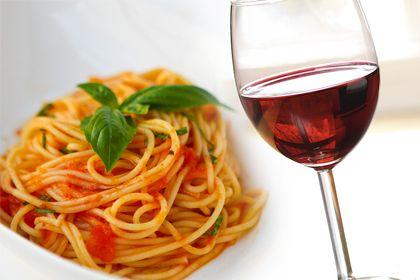 El vino y la comida. Cuenco de tallarines o espaguetis con salsa roja y albahaca, junto a una copa de vino tinto.