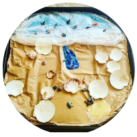 seaside scene tuff tray with sandpaper sand, shells and natural resources and blue material under bubble wrap for the sea