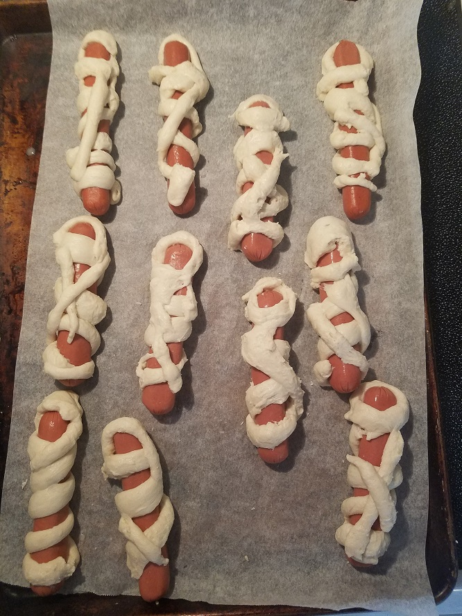 this is how to make a mummy dog for Halloween out of hot dogs and pizza dough or refrigerator biscuits.