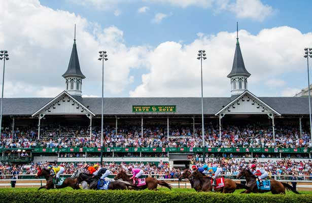 view of the twin spires at churchill downs with fans in the stands and horses running past on the track and a blue sky with white clouds above