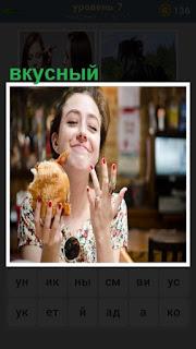 девушка ест вкусный пирожок с довольным видом на лице
