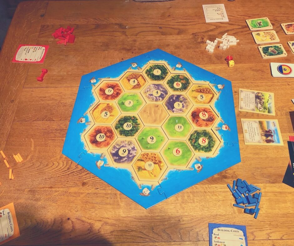 Setting up the board game Catan. The board pieces have been put together on a wooden table, each resource board piece has an oval number card on it.