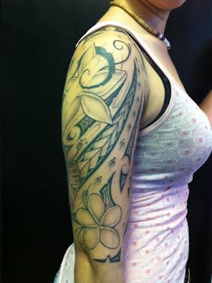 chica con tatuaje maori de flor en el brazo