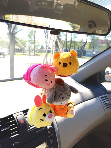 winnie the pooh piglet eeyore tigger rabbit disney tsum tsum characters fuzzy dice hanging from the rear view mirror of a car in the sunshine