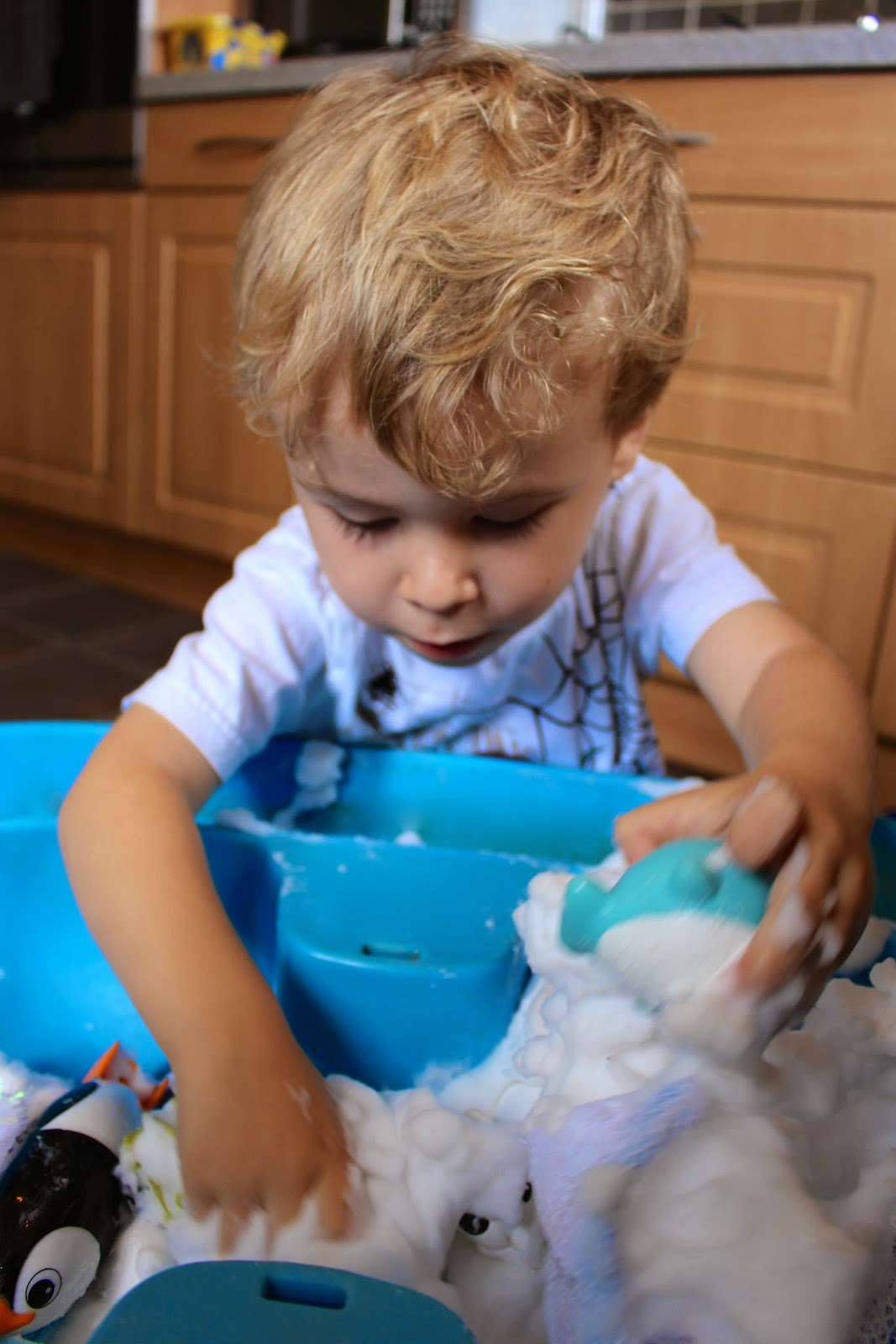 Snowy sensory play activity for toddlers and preschoolers.  Create a simple small world winter snow scene using foam soap, penguins and polar bears.