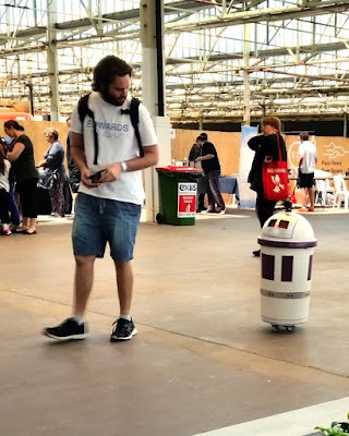 Jaidyn Edwards is walking towards the left of the picture. Following behind is a white cylindrical robot with a rounded top. There are wheels underneath. There are windows in its top presumably for the camera. Jaidyn is wearing a white t-shirt and blue shorts with black shoes. The T-shirt says Edwards Electronics. Black straps of a backpack are over his shoulders. He is holding a remote control unit in his hands as he looks back towards his robot.