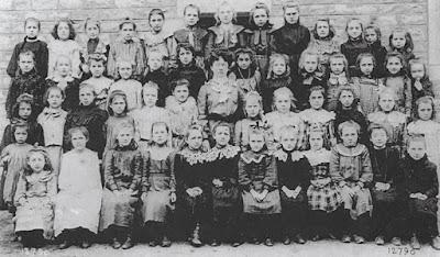 """Ecole de filles de la rue Centrale, peut-être la classe de Mlle Rivet aux """"yeux myopes, mais pourtant vifs sous le binocle pédagogique"""" (citation du """"Pays Noir"""") (Collection musée)"""