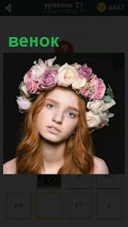 Голова девушка украшена венком из красивых цветов, из под которого спускаются волосы ниже плеч