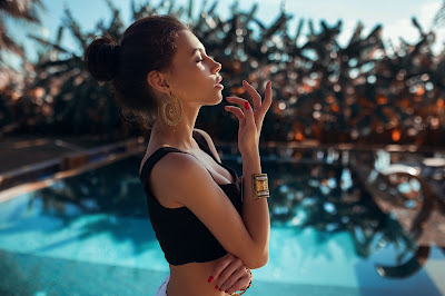 Linda chica de perfil con piscina de fondo