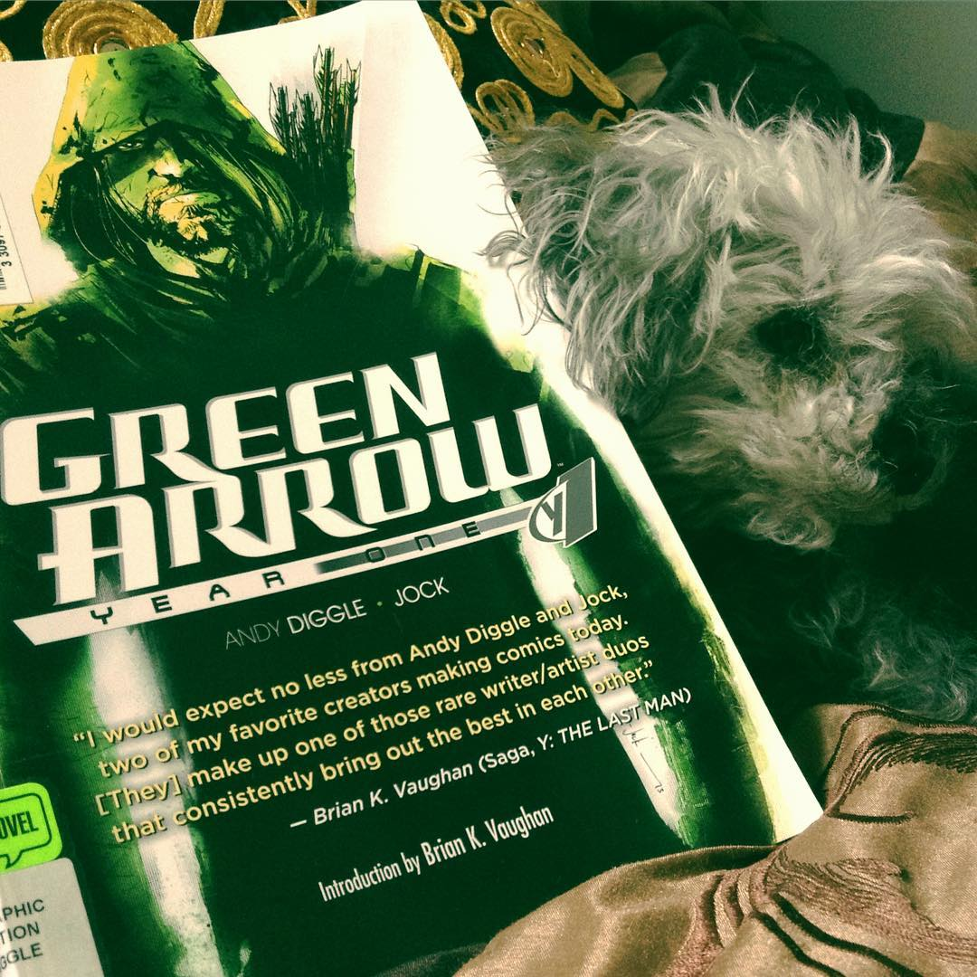 A green-tinged photo of Murchie lying beside a trade paperback copy of Green Arrow Year One with a portrait of the titular character on the cover.
