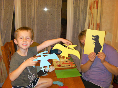 dinosaur diorama cut-out display with pterodactyl and tyrannosaurus rex