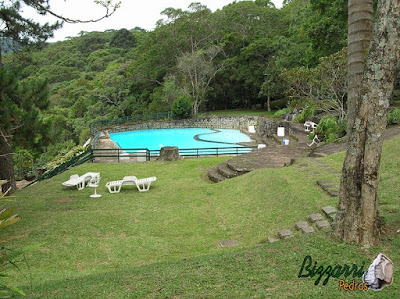Cascata de pedra na piscina com pedra natural, sendo a construção da piscina com pedra de rachão de granito bruto.