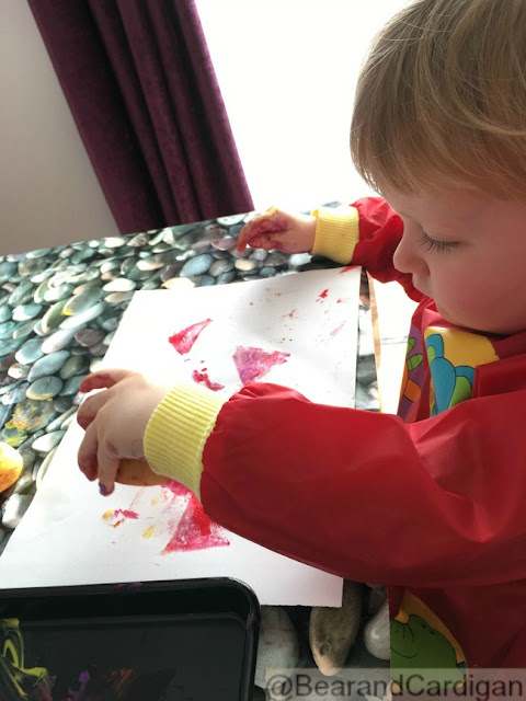 toddler holding potato stamp over paper