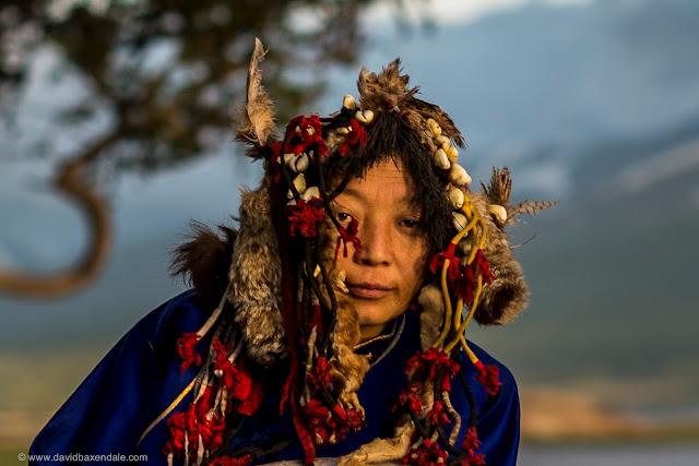 Xamã mongol paramentada com uma roupa azul e adereços de penas e outras coisas na cabeça.