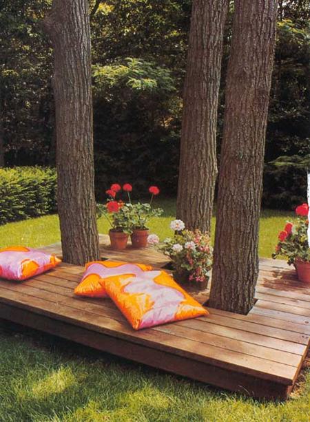 jardim com deck integrando as árvores com floreiras e almofadas